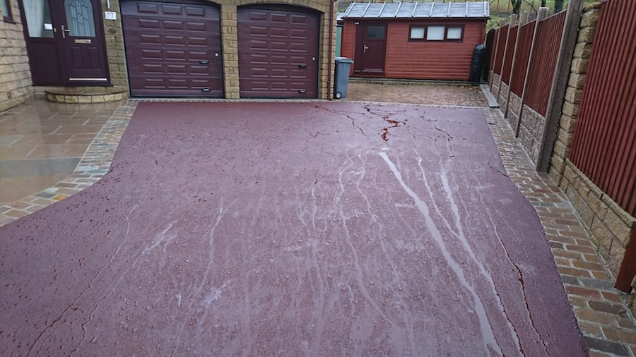 red tarmac drive after looking up to garage doors