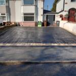 black tarmac drive with with Indian stone setts border